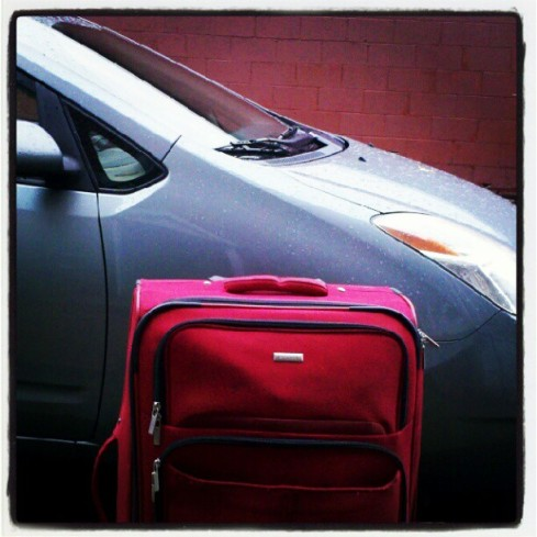 prius with suitcase on a road trip